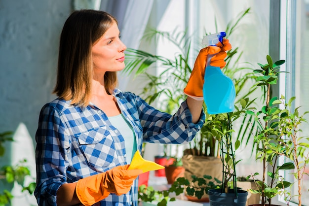 Young woman holding yellow napkin spraying on window glass