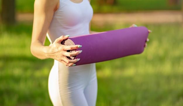 Молодая женщина, держащая коврик для йоги после окончания урока в парке