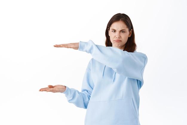 당신의 카피 공간을 잡고 찡그린 얼굴을 하는 젊은 여성, 그녀가 손에 들고 있는 것을 싫어하고, 물건을 보여주고, 불평하고, 흰 벽에 화를 내며 서 있습니다