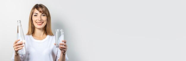 Молодая женщина держит бутылку и стакан с чистой водой. баннер. концепция жажды, тепла, здоровья и красоты, водного баланса