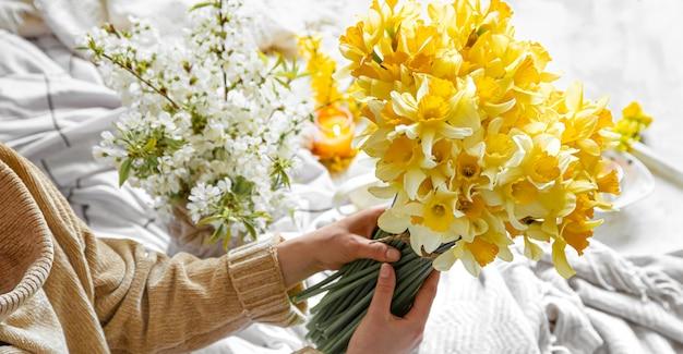 젊은 여자는 수 선화 꽃다발을 보유하고있다.