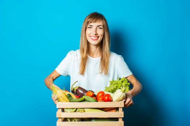 若い女性は青の新鮮な野菜の箱を保持しています。豊作コンセプト、天然物