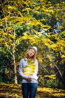 Молодая женщина держит в руке ветку с желтыми листьями