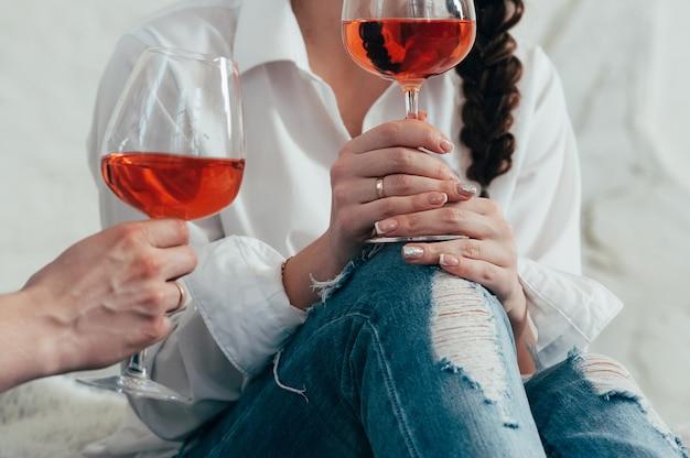 若い女性は、ロマンティックなデートのグラスローズワインを保持します