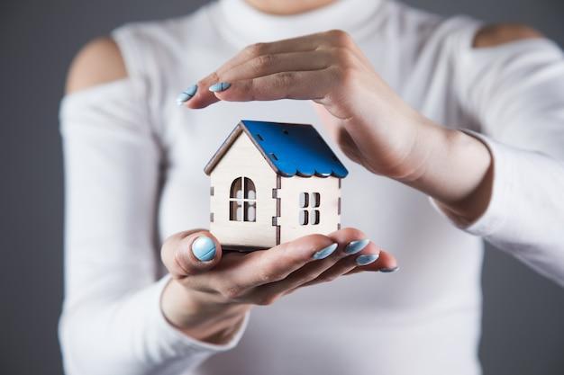 젊은 여자는 회색 벽에 그녀의 손에 집을 보유