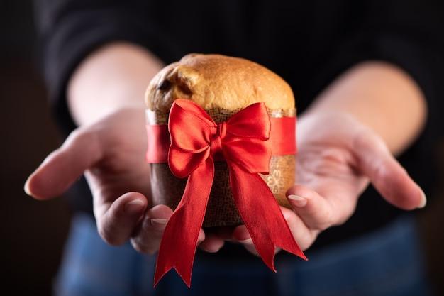 若い女性は典型的なクリスマスケーキのパネトーネを保持します