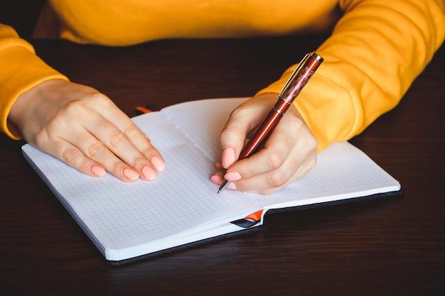 若い女性は彼女の左手にペンを保持し、空白のノートにメモを書き込みます。国際左利きの日