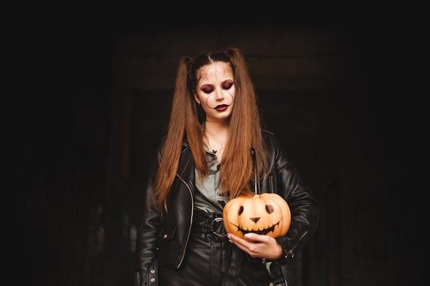Молодая женщина держит в руках тыкву раскрашенная тыква