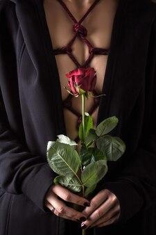 Молодая женщина держит розу в руке