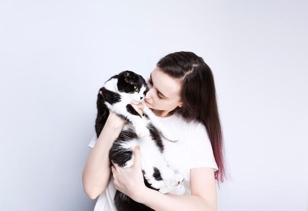 Молодая женщина держит взрослую кошку, серый фон