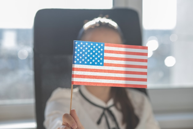 Young woman holds american flag in her hand, sits in an armchair in an office at a table