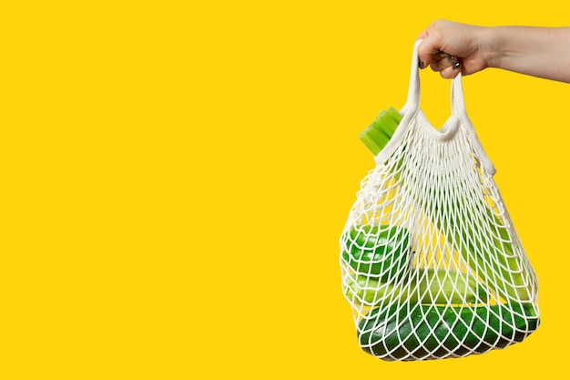若い女性は黄色の背景に緑の野菜とエコストリングショッピングバッグを保持します。
