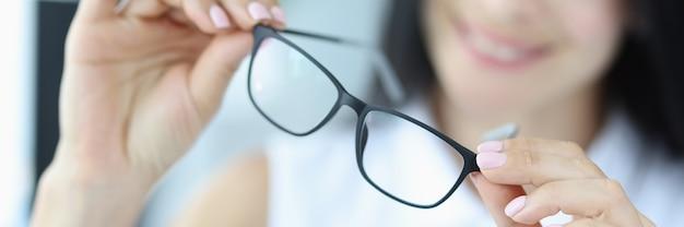若い女性は手に視力のための黒い眼鏡を持っています