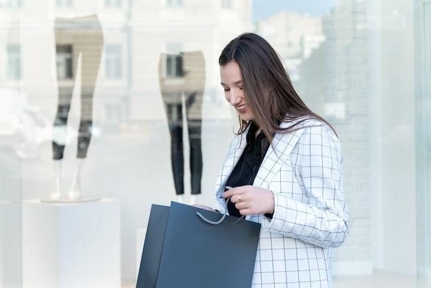 若い女性は、ショーケースを背景に購入するための黒いパッケージを保持しています。セール。