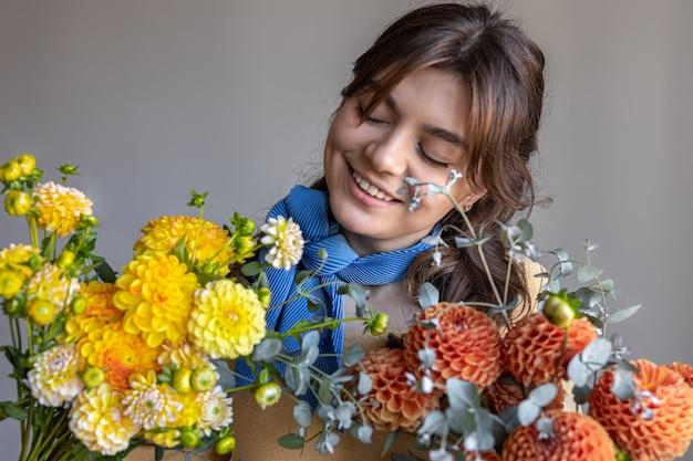 Una giovane donna tiene in mano un mazzo di fiori di crisantemo