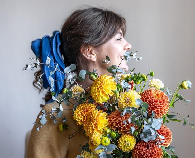 Una giovane donna tiene in mano un mazzo di crisantemi