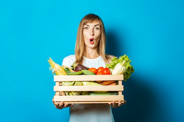 Young woman holds a box with fresh vegetables on blue. good harvest concept, natural product