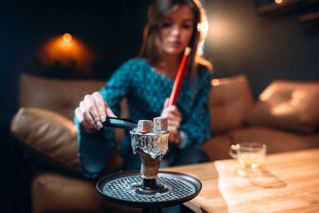 Young woman holds coal with tongs, smoking hookah at the bar, tobacco smokes at night club