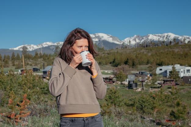 若い女性はコーヒーマグを持って、キャンプ場で寒い朝に会います。ロマンチックなキャンプ旅行のコンセプト。