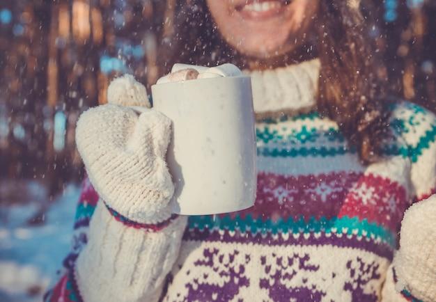 젊은 여자는 겨울 숲에서 마시멜로와 함께 커피 한 잔을 들고