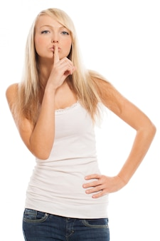 Young woman holds finger on lips