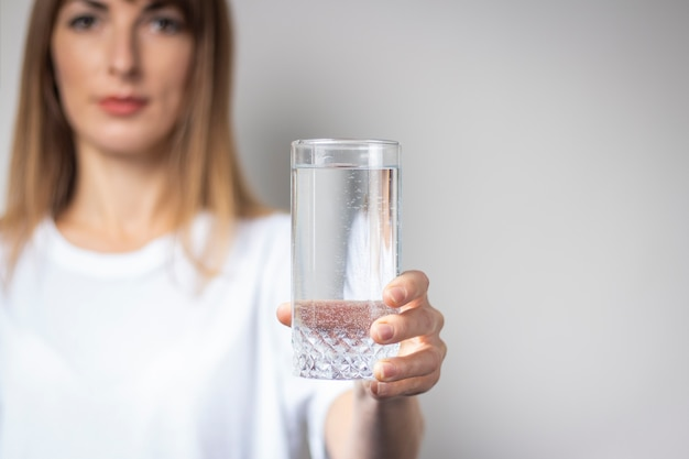 Young woman holds a glass with clear water on a light surface