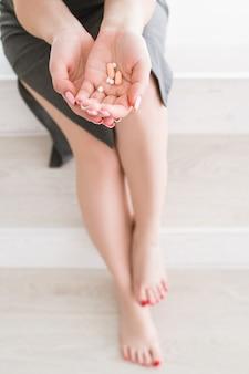 若い女性は一握りの錠剤を持っています。自宅でのヘルスケア、ビタミン、薬の治療、薬物中毒のクローズアップ画像