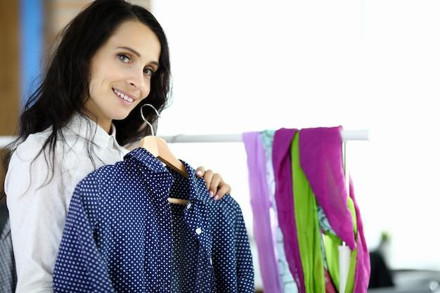 若い女性は縫製ワークショップで彼女の手に黒いシャツとハンガーを保持します