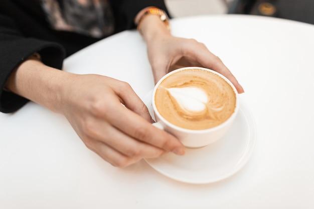 若い女性は、カフェの白いテーブルに座っている熱い甘いカプチーノとカップを手に持っています。コーヒーグルメにとっておはようございます。コーヒーと女性の手の上面図。閉じる。