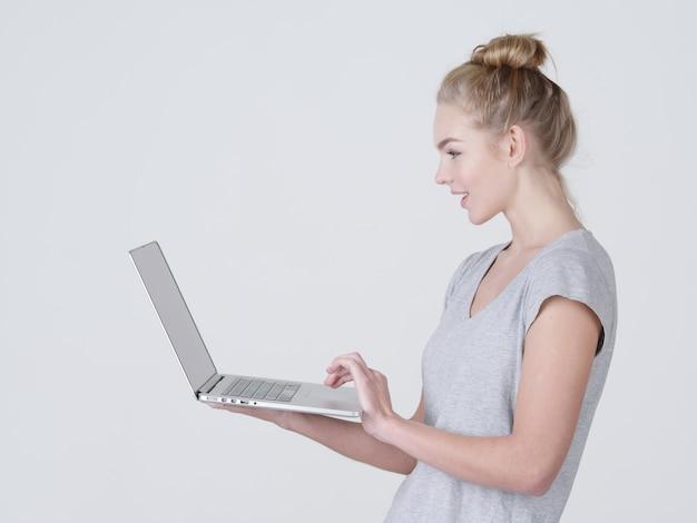 Молодая женщина держит ноутбук в habds. улыбающаяся кавказская девушка с ноутбуком позирует в студии