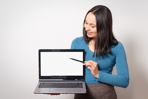 Young woman holds a laptop and points at its screen blank for inserting an image