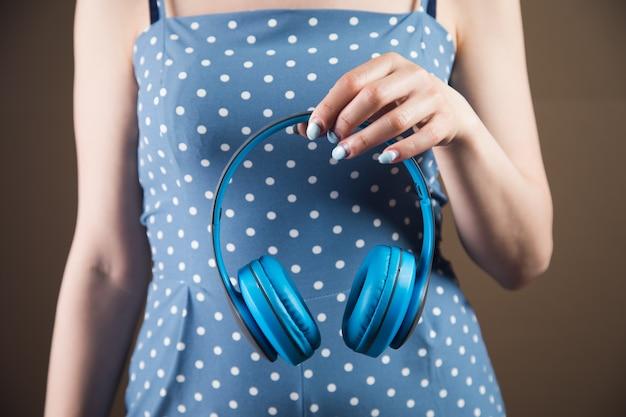 젊은 여자는 갈색 배경에 큰 헤드폰을 들고