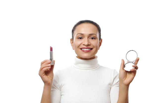 Young woman holds a lipstick and a mirror in the hands while posing with a beautiful toothy smile to the camera