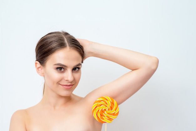 Young woman holds lollipop on her armpit.