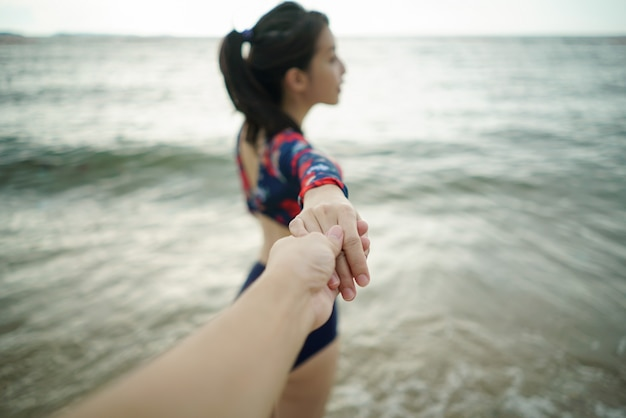 Young woman holds man's hand leading him on beach