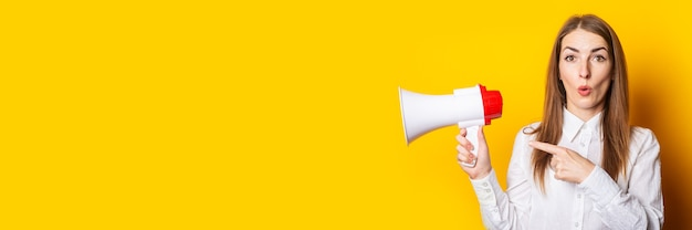 Young woman holds a megaphone in her hands and points her finger at it on a yellow background