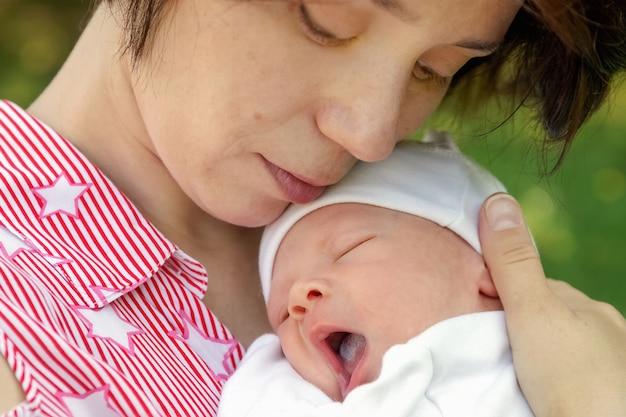 若い女性は彼女の胸にそれをつかんで彼女の腕で生まれたばかりの赤ちゃんを保持します