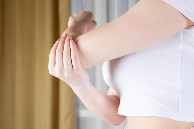 젊은 여자는 그녀의 손을 밖으로 보유합니다. 집에서 운동