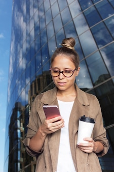 A young woman holds a paper cup of coffee looking at a mobile phone screen near a business center
