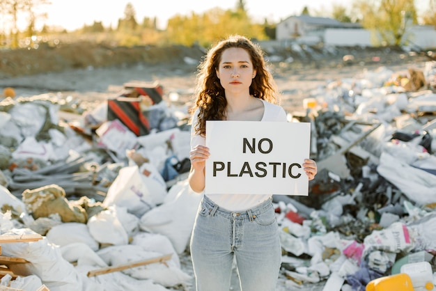 A young woman  holds a poster. the inscription no plastic. showing a sign protesting against plastic pollution.