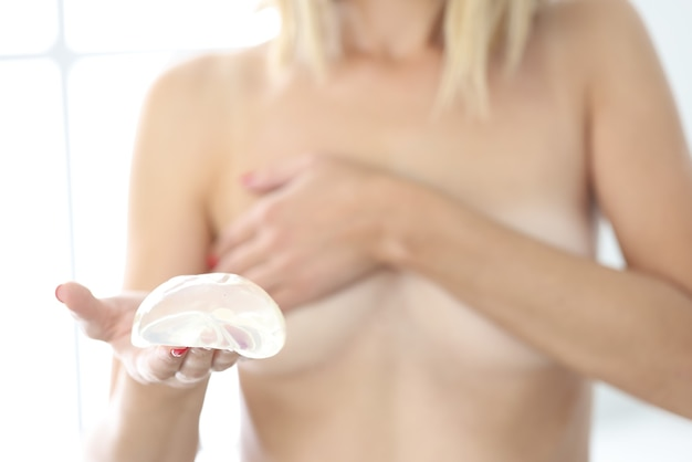 Young woman holds silicone breast implant in hand