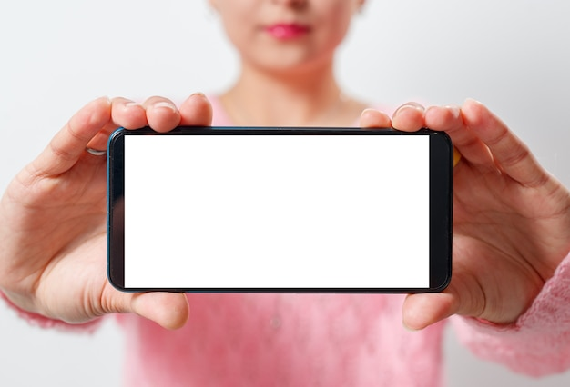 Young woman holds the smartphone horizontally with a white screen with a place