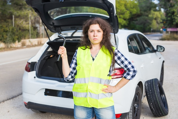 Young woman holds a spanner in the wall of a broken car