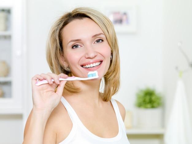 若い女性は、歯磨き粉で歯ブラシを保持します