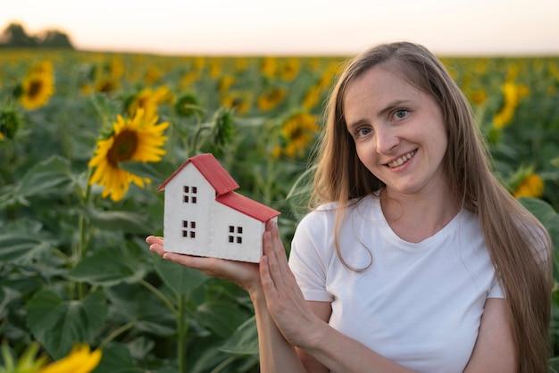 若い女性は手のひらにおもちゃの家を保持します