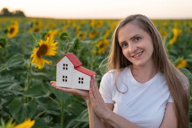 Young woman holds toy house in the palm