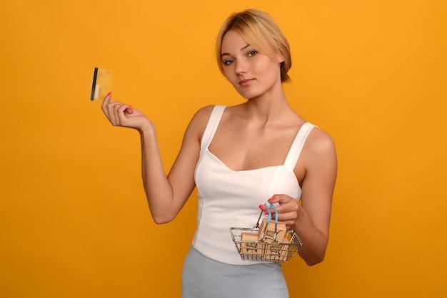 Молодая женщина держит корзину для товаров металла игрушки с синей пластиковой ручкой и кредитной картой, изолированной на фоне. образ