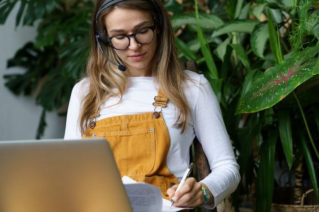 젊은 여성 가정 정원사 또는 꽃집 장식가는 온라인으로 고객과 주문 예산에 대해 논의합니다.