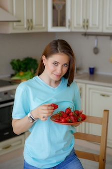 Young woman at home in the kitchen eating fruit