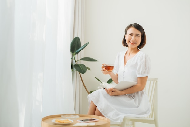 Young woman at home sitting near window relaxing in her living room reading book and drinking tea